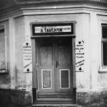 93. Jen o padesát metrů dál provozoval svou živnost pan Tauchym holič a kadeřník. Jeho reklamní štít upozorňoval, že umí dělat mikáda všech druhů a provozuje i divadelní líčení. Po roce 1945 se z holičství stala na dlouhá léta mlékárna, která zanikla v 70. letech. Přestavěný dům stojí dodnes. (Autor fotografie A. Tauchym, sbírka Hornické muzeum Rudolfov).